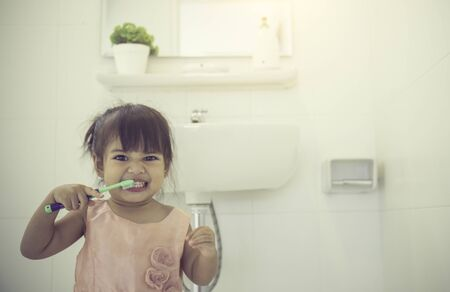 Little cute baby girl cleaning her teeth with toothbrush in the bathroom