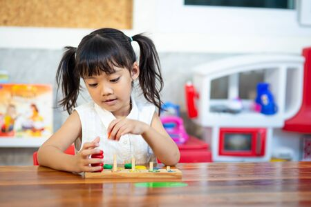 child little girl playing wooden toys