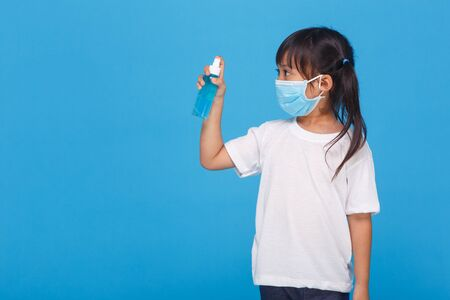 Cute Asian girl wearing a mask and washing her hands with alcohol to prevent spreading the disease on a white background. Prevention of the spread of influenza virus Coronary COVID-19 influenza
