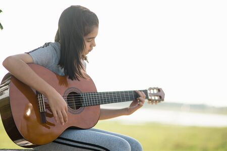Lovely girl,playing guitar, singing ,music or happiness concept, sunset warm light tone effect.