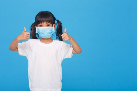 Coronavirus Covid-19 pm2.5.Online education.Little girl wearing face mask show thumbs up for good and happy at home. Covid-19 coronavirus.Stay home.Social distancing.New normal behavior. Archivio Fotografico