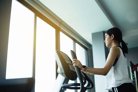Asian girl Exercise Elliptical cardio running workout at fitness gym taking weight loss with machine aerobic for slim and firm healthy lifestyle