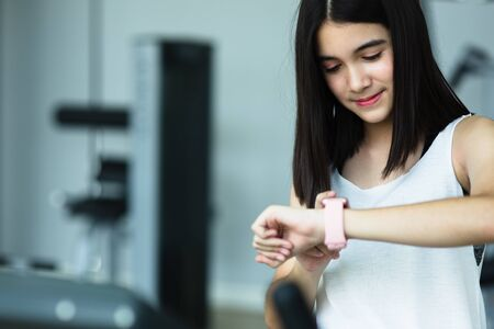 A little girl  looks at smart watch after training in gym. Healthy concept. Female after workout session checks results on watch.Children's sport concept