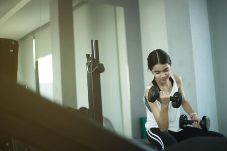 Young beautiful girl doing exercises with dumbbell in gym. Standard-Bild