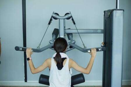 young fitness girl execute exercise with exercise-machine in gym Standard-Bild