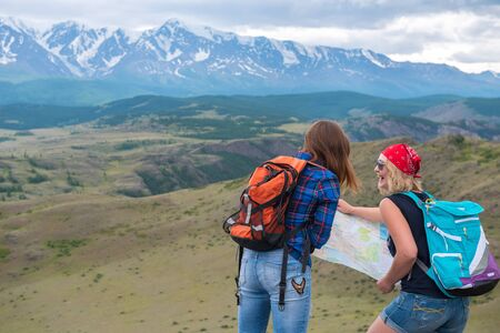 Two girls look at the map on the background of mountains and think where to go