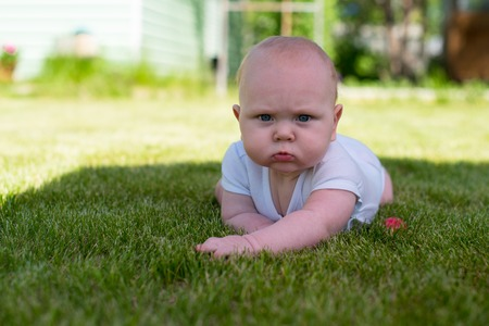 frowns: baby is lying on the grass in the garden and frowns