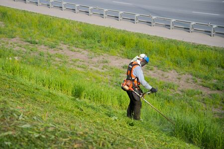 off cuts: The worker in a uniform and mask cuts off a thick grass
