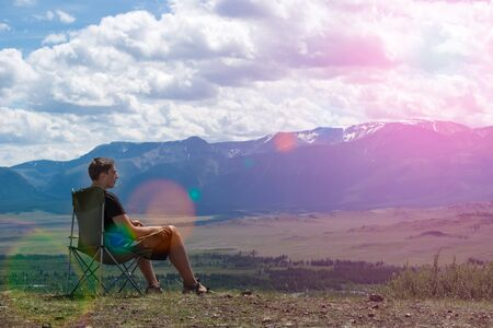 boy sitting on a chair in the mountains and looks into the distance