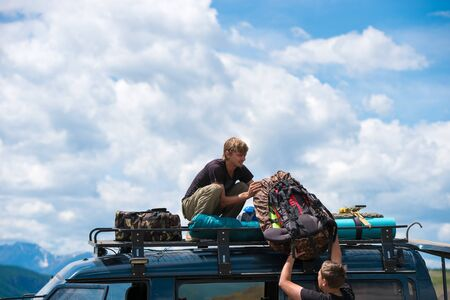 the man gives another man a backpack on the roof of the car