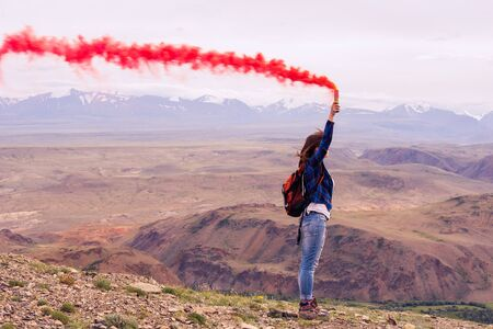 smoking woman: a girl with red smoke on the mountain