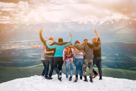 친구 그룹은 산 꼭대기에 오른 행복합니다. 그들은 포옹과 점프. 거리를 카메라와 다시보고 있습니다. 스톡 콘텐츠