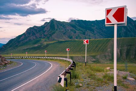 breakage: Landscape. The road in the mountains turns to the left. Ahead of breakage. Left turn sign. Stock Photo