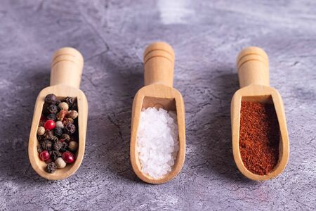 Spices for cooking in spoons on a gray background