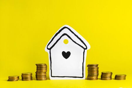 Accumulating money for your home on a yellow background Stok Fotoğraf