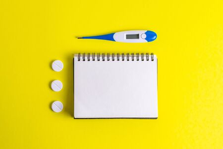 Hands with a notebook in rubber gloves with a thermometer on a yellow background