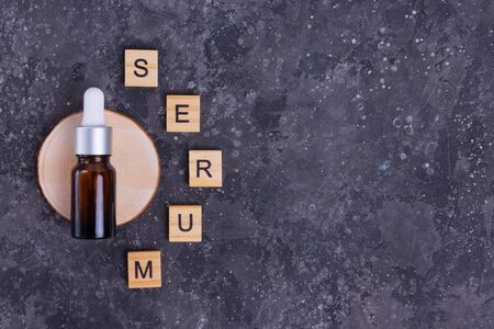 Moisturizing serum with collagen and mucin of a snail for face skin against wrinkles and acne in a glass brown bottle with serum letters on a gray background
