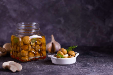 Fermented canned champignon mushrooms in a white plate for appetizers and in a glass jar with garlic, bay leaf and a white napkin with dill