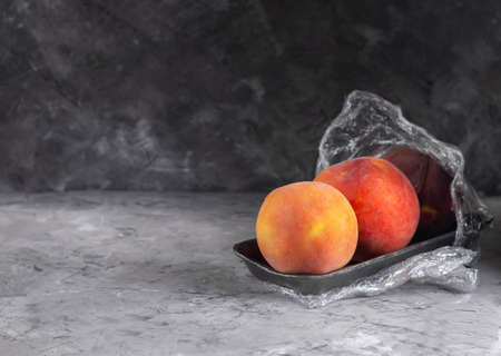 Fresh peaches in a plastic container with cling film on a dark background