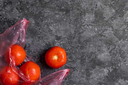 Tomatoes in a pink plastic bag on a gray background
