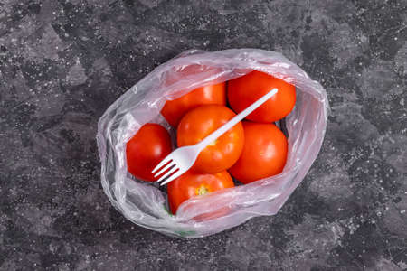 Tomatoes in a transparent plastic bag with a fork on a gray background