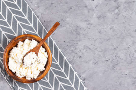 Cottage cheese in a wooden plate with a wooden spoon on a gray napkin