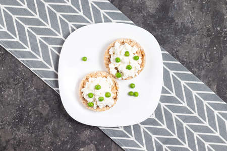 Crispbreads with cottage cheese and green peas on a white plate on a gray background Archivio Fotografico