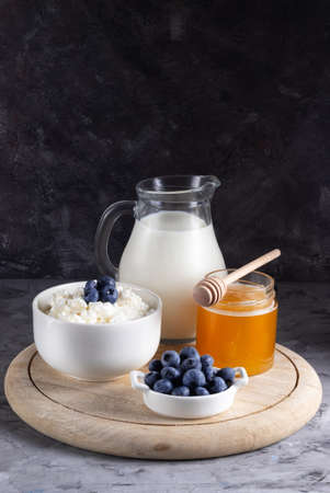 Grain cottage cheese in a white plate with blueberries with sour cream, milk and honey on a wooden stand