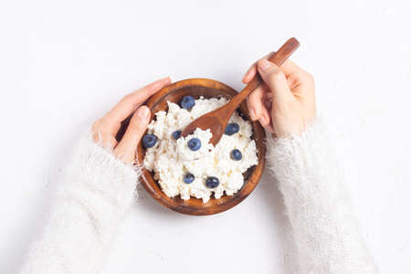 Girl in a white sweater holds a plate with grained cottage cheese and blueberries in a spoon