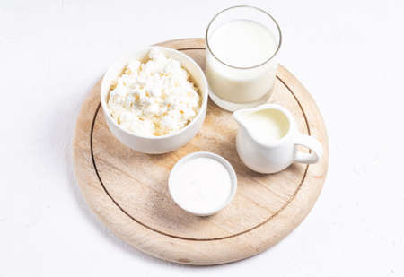 Grain cottage cheese, sour cream, cream and milk on a wooden round stand in a high key