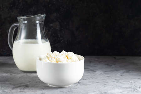 Grain cottage cheese in a white plate with jugs of milk on a dark background