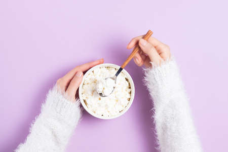Girl in a white sweater holds a plate with grained cottage cheese in a spoon on a pink background Zdjęcie Seryjne