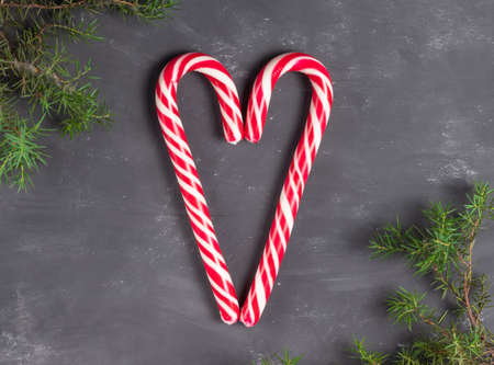 Heart made of sweets of red and white staffs on a chalk background with fir branches