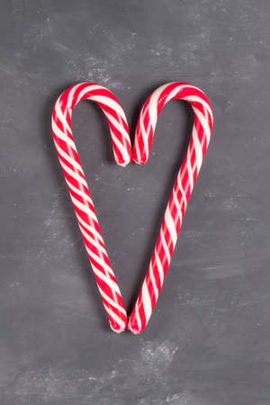 Red and white christmas candy staffs on dark background Imagens
