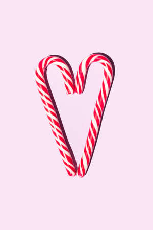 Red and white christmas candy staffs in the form of a heart on a pink background