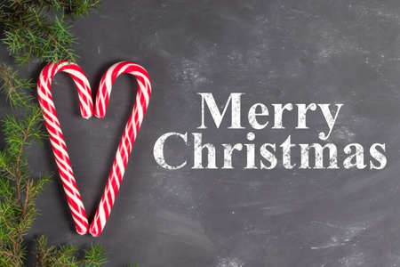 Heart made of candy staffs on a chalk background with fir branches with the inscription Merry Christmas