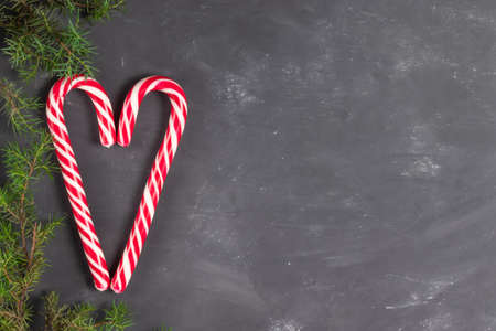 Heart made of candy staffs on a chalk background with spruce branches copy space