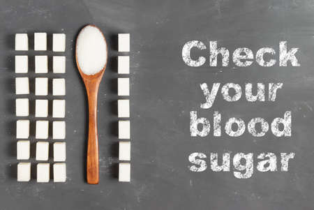 Lettering Check your blood sugar level with chalk on a gray background with sugar lumps and an eco wooden spoon with sugar for World Diabetes Day November 4th