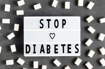 The inscription Stop diabetes on a white board on a gray background with sugar cubes for World Diabetes Day 4 November