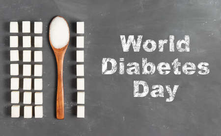 World Diabetes Day lettering in chalk on a gray background with sugar lumps and an eco wooden spoon with sugar
