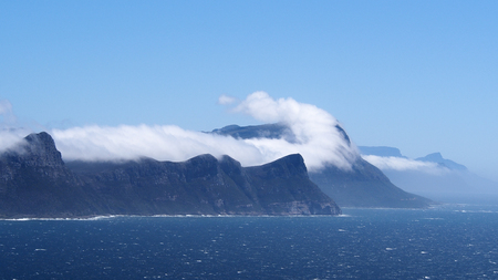 cape of good hope: Clouds over cliffs and blue sea and under sky at Cape of Good Hope in South Africa Stock Photo