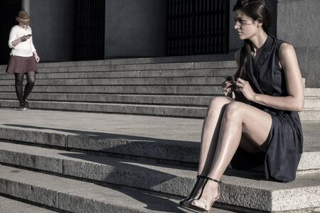melancholia: Beautiful woman with very nice legs tearing her hair out feeling alone Stock Photo