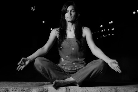 body consciousness: Beautiful woman practicing meditation (Radja Yoga) at night in the city. Mindfulness  calm concept.