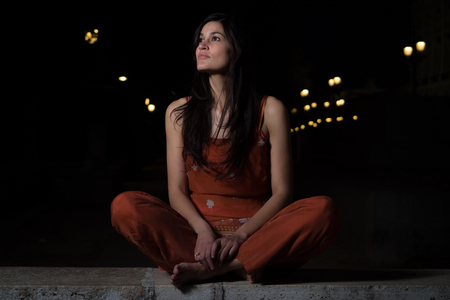 Beautiful woman with dark hair and big eyes chilling out at night in the city Stock Photo
