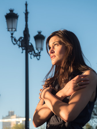 melancholia: Beautiful girl feeling alone against blue sky with the golden light of the sunset (homesick concept)