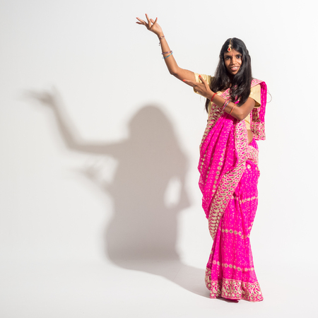 bindi: Beautiful young indian woman dancing Bollywood and wearing a traditional sari on white background