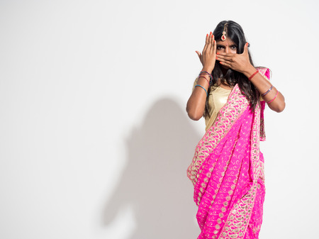 Beautiful and enigmatic young indian woman wearing a traditional sari on white background