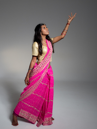 Beautiful young indian woman with long and dark hair acting and wearing a traditional sari on gray background