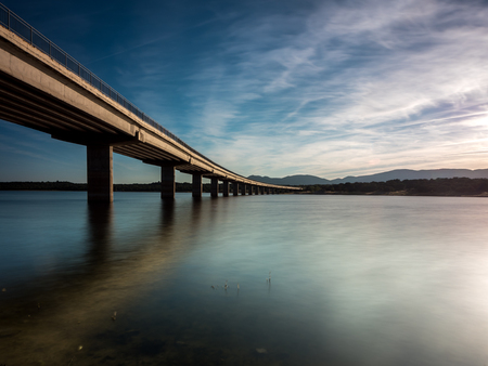 still water: Long bridge over a lake with still water at evening, blue hour (calm scene, serenity concept) Stock Photo