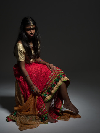 sari: Beautiful young indian woman with long and dark hair and nice lips sat wearing a sari Stock Photo